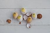 Bemalte Ostereier und Eierschalen auf weißem Holz