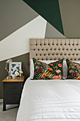 Double bed with tall headboard against wall with geometric pattern in bedroom
