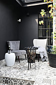 Armchairs and brazier on terrace with dark walls and ornate floor tiles