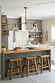 Counter with wooden barstools in open-plan renovated kitchen with grey wall
