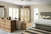 Schlafbereich mit Doppelbett, Kleiderschrank, Ausziehcouch und antikem Apothekerschrank in offenem Wohnraum