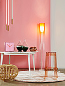 Designer standard lamp, clock and glass vases on table, transparent bar stool and rattan stool in front of pink wall