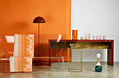 Transparent designer sofa, standard lamp and vases on console table against orange wall