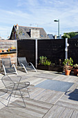 Sun loungers and designer chair on roof terrace