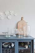 Old bottles, cake stands and chopping board on top of glass-fronted cabinet