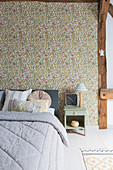 Bed against wall decorated with floral wallpaper in period building