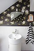 Vintage-style mirror on dark floral wallpaper above sink