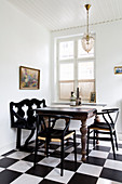 Designer chairs around old wooden table on chequered floor