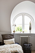 Cushions and sheepskin on bed next to arched window