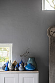 Sammlung von Vasen in Blau und Grau vor grauer Wand