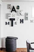 Arrangement of letters in shades of grey on wall