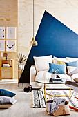 Couch mit Kissen und Coffeetable vor Sperrholzwand mit blauem, geometrischem Muster
