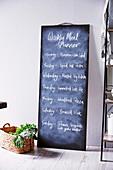 DIY-Kreidetafel mit Wochenmenü an die Wand gelehnt, davor Korb mit Gemüse