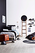 Black and white youth room with ladder and DIY shelf made of skateboards