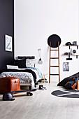 Schwarz-weißes Jugendzimmer mit Leiter und DIY-Regal aus Skateboards