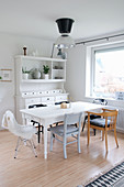 Various chairs around dining table in front of white dresser
