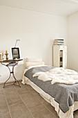Einzelbett mit Schaffell, Bücherschrank und Vintage Metalltisch im Schlafzimmer