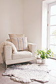Cushion on white leather armchair and sheepskin rug next to French windows
