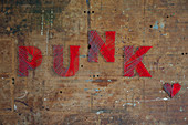 'Punk' written in red lettering on old wooden door