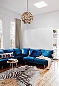 Blaue Sitzgarnitur und Zebrafell in hellem Wohnzimmer mit Holzdielenboden