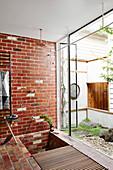 Dusche mit Ziegelwand und Gartenzugang