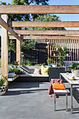 Modern terrace with corner bench, outdoor kitchen and pergola