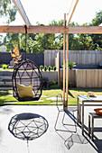 Hammock chair on sunny terrace with pergola in modern garden