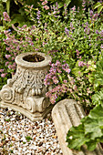 Capital and stone pillar between gravel and plants