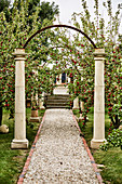 Arbor with stone columns above the gravel path in the apple orchard