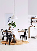 Black metal chairs around round wooden table with baluster base