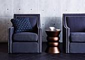 Kupferfarbener Beistelltisch zwischen blauen Sesseln mit Polsternägeln