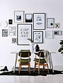 Black and white picture wall above the dining table with green chairs