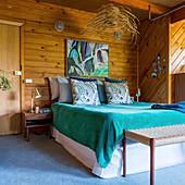 Doppelbett mit türkisfarbener Tagesdecke im Schlafzimmer mit Holzverkleidung