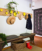 Rustic wooden bench, basket and rubber boots, wooden wardrobe with hats above