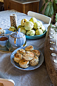 Pastries, crockery and fruit on a country dining table