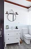 Waschtischmöbel neben Toilette im Badezimmer mit weißen Wandfliesen