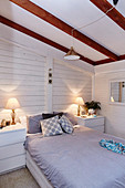 Bedroom with white painted wooden paneling in the attic