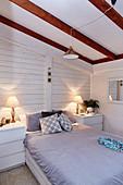 Schlafzimmer mit weiß gestrichener Holzverkleidung im Dachgeschoß