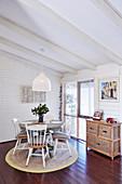 Runder Tisch mit Holzstühlen auf Teppich im Essbereich mit weißer Holzverkleidung