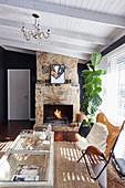 Klassiker Lederstuhl mit Felldecke und Zimmerpflanze vor Kamin im Wohnzimmer