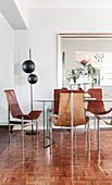 Designer chairs made from leather and metal around dining table on parquet floor
