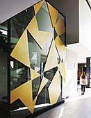 Geometrische Formen in Gold an der Glaswand zum Treppenhaus