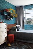 Blau gemusterte Tapete im Kinderzimmer, Regale überm Bett