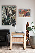 Side table, leather sofa and sculpture below two abstract paintings