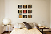 Pictures arranged in a square above a double bed