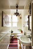 Chandelier and bathtub in niche in narrow L-shaped bathroom