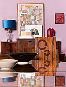 Bowls on dining table and chair with inlaid veneer backrest in front of sideboard
