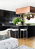 Dark fitted kitchen with counter and barstools in open-plan interior