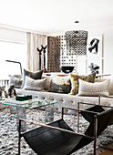 Cushions on sofa, glass coffee table and designer chair in bright living room