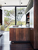 Modern kitchen with dark wooden cupboards and glass wall